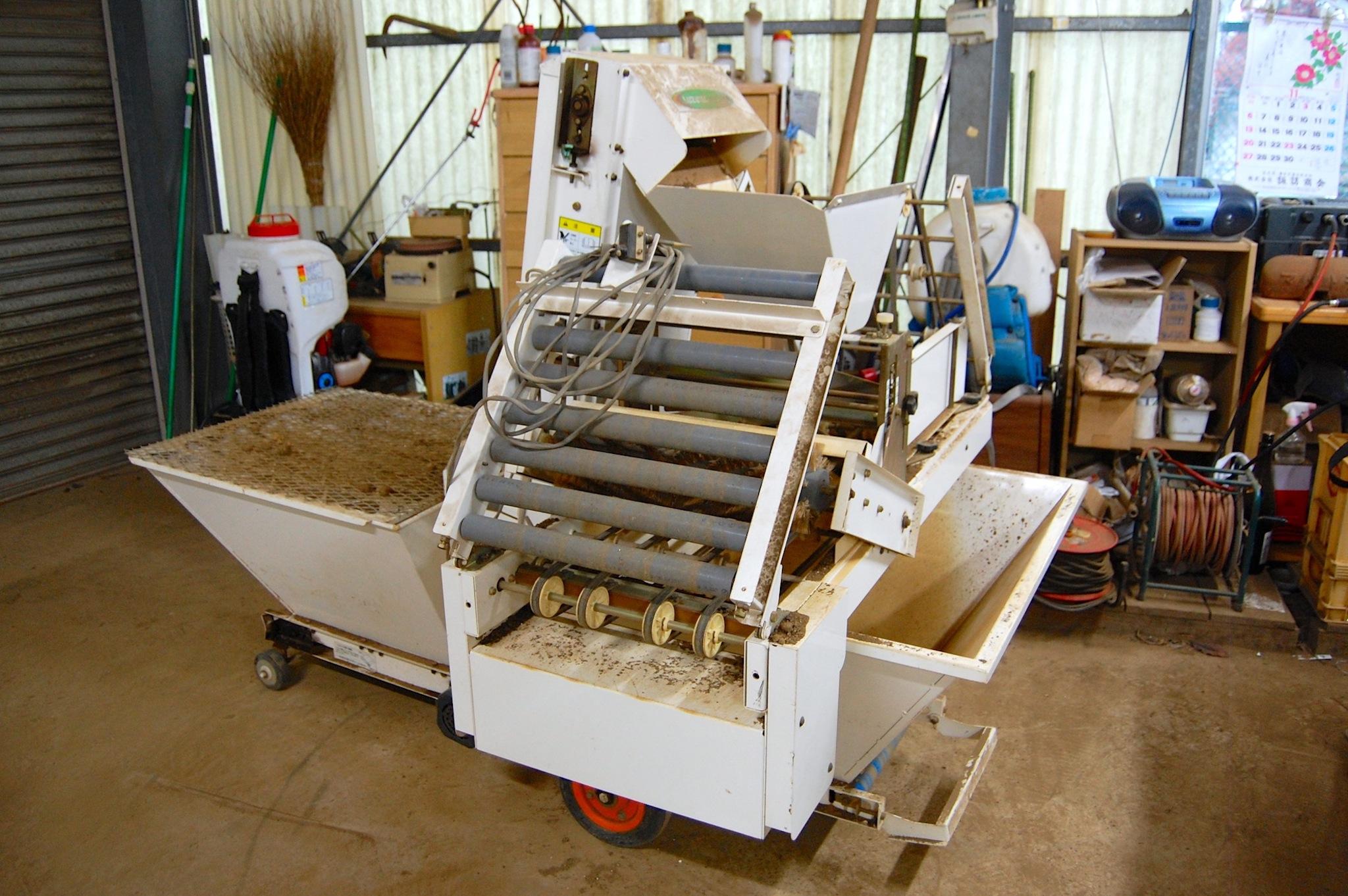 作った土を1つずつポットに入れていく機械
