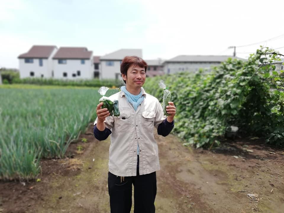 収穫したいんげんとピーマンを持つ冨澤剛さん